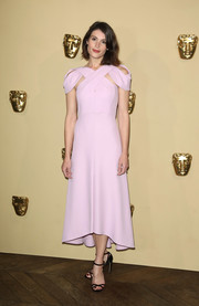 Gemma Arterton paired her dress with black cross-strap sandals by Jimmy Choo.