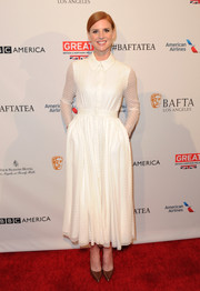 Sarah Rafferty looked prim in a white gown with polka dot sheer sleeves and folded collar for a posh outfit.