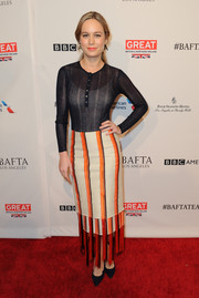 Brie Larson rocked a sheer black top that she paired with a high-waisted orange and white fringed midi skirt.