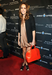 Louise Roe injected a bold dose of color into her red carpet look with an orange patent Vernis Alma bag.