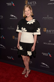 Rosamund Pike cut a bold silhouette in a black-and-white floral jacquard dress by Alexander McQueen at the BAFTA Los Angeles tea party.
