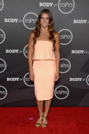 Danica Patrick styled her dress with gold cross-strap sandals.