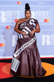Lizzo was eye candy — literally — in a one-shoulder chocolate-wrapper gown by Moschino at the 2020 BRIT Awards.