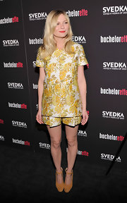 Kirsten Dunst kept it color-coordinated with her suede mustard platforms matching her floral shirt and short combo.