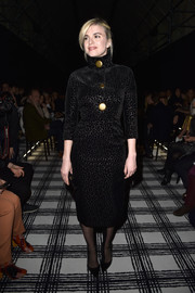 Cecile Cassel made a stylish appearance at the Balenciaga fashion show in a high-neck, gold-buttoned LBD from the label's Pre-Fall collection.