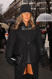 Anna dello Russo attended the Balenciaga fashion show sporting an all-black outfit, finished off with an elegant Valentino crocodile purse.