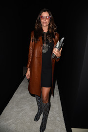 Christina Pitanguy layered a brown leather coat over an LBD for the Balmain fashion show.