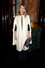 Alexandra Golovanoff kept warm in style with a retro-chic white cape during the Balmain fashion show.