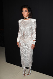 Kim Kardashian cut a strong silhouette in a broad-shouldered white Balmain dress during the label's fashion show.