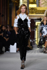 Natalia Vodianova worked a black PVC jumpsuit layered over a cold-shoulder button-down at the Balmain runway show.