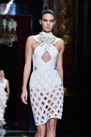 Kendall walks the Balmain runway in an all-white cutout.
