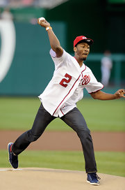 Basketballer John Wall tossed the first pitch at a Washington Nationals game, wearing the Nationals' white and red jersey.