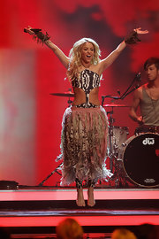 Shakira jumps on stage in a voluminous fringed skirt over her skimpy bodysuit.