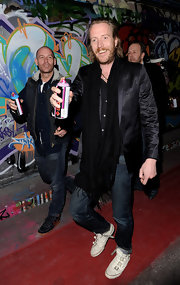 Rhys Ifans added a third layer to his black-on-black look with a fringed scarf.