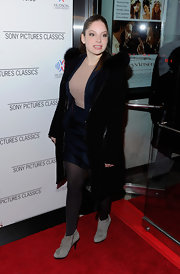 Anna Hopkins kept warm in a pair of gray suede ankle boots. She wore the cold weather essentials over black tights.