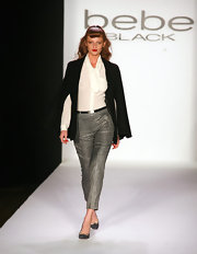 Cintia Dicker epitomized a stylish modern woman as she wore a corporate-inspired ensemble featuring a sheer button-down shirt, a black blazer, and metallic pants at the Fall 2012 presentation of Bebe.