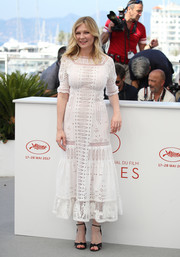 Kirsten Dunst paired her cute dress with black knot-detail sandals by Gucci.