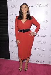 Tina is vivacious in a red cocktail dress. She wears leopard print pumps and a thick black belt.
