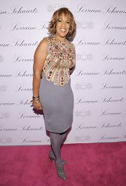 Gayle wears a decorative gray sweater dress with gray tights and pumps.