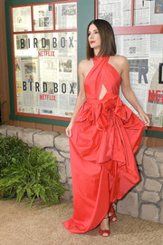 Sandra Bullock went for bold glamour in a red Martin Grant halter gown with a crossover bodice and a sculptural skirt at the New York screening of 'Bird Box.'