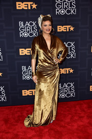Andra Day was all aglow in a draped gold wrap gown at the Black Girls Rock! show.