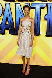 Letitia Wright was feminine and elegant in a strapless gold Rami Al Ali dress with an embellished midsection at the European premiere of 'Black Panther.'