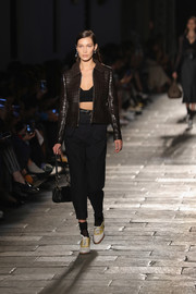 Bella Hadid sported a pair of loose, high-waisted pants with her stylish jacket.