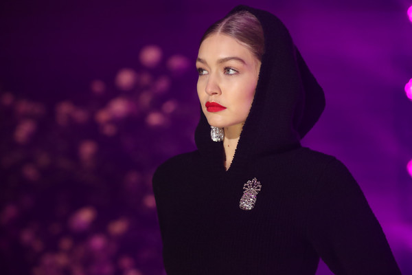 Gigi Hadid donned a black hoodie adorned with a pineapple crystal brooch for the Brandon Maxwell fashion show.