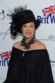 Sue Wong turned heads at the BritWeek Celebrates Downton Abbey event with her elaborate get-up, topped off with a flower statement necklace and a fancy hat.