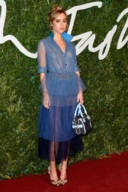 Suki Waterhouse topped off her outfit with a small blue denim and leather bowler bag, also by Burberry.