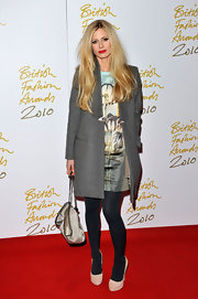 Laura Bailey wore nude suede pumps over navy hued tights. The dark tights really make the heels pop.
