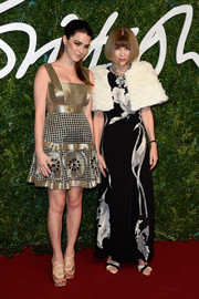 Bee Shaffer glimmered on the British Fashion Awards red carpet in a gold Alexander McQueen mini dress with a floral and grid-patterned skirt.