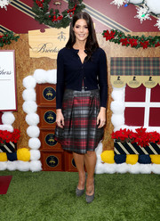 Ashley Greene layered a navy Brooks Brothers cardigan over a plaid dress for the brand's annual holiday celebration.