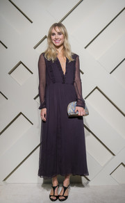 Suki Waterhouse polished off her look with a crescent-shaped metallic clutch.