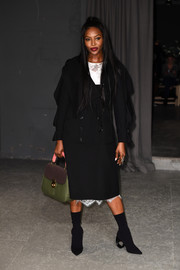 For a pop of color, Naomi Campbell accessorized with a green, tan, and pink top-handle tote.
