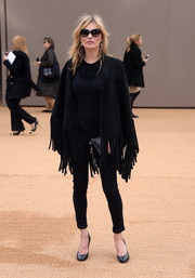Kate Moss stayed warm in a fringed black Burberry cape as she arrived for the brand's fashion show.