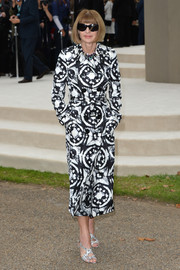 Anna Wintour matched her coat with her signature Manolo Blahnik double-crisscross-strap sandals (she traded in her usual nude for this printed pair though).