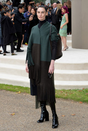 Erin O'Connor arrived for the Burberry Prorsum fashion show wearing a fringed tricolor poncho from the brand.