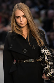 Cara Delevingne showed her silhouette in her trench by wearing a metal belt on top of it.