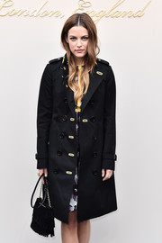 Riley Keough attended the Burberry fashion show carrying a fringed black suede bag from the label.