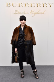 Noomi Rapace arrived for the Burberry fashion show wearing a luxurious two-tone fur coat from the label.