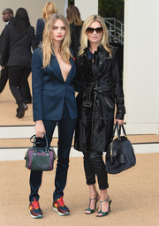 Cara Delevingne flashed some cleavage in a blue Burberry pantsuit worn shirtless during the label's fashion show.