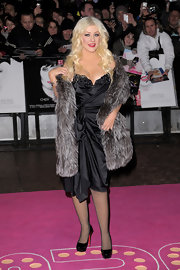 Christina dons a dramatic fur stole with this saucy burlesque look.