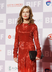Isabelle Huppert paired a black snakeskin clutch with her evening dress at the Busan International Film Festival.