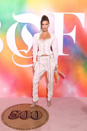 Bella Hadid hit the #BoF500 2018 wearing a funky cream pantsuit by Andreas Kronthaler for Vivienne Westwood.
