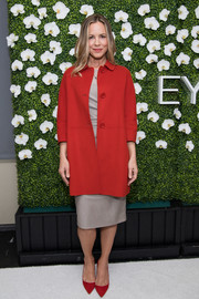 Maria Bello attended the Eye Speak Summit wearing a stylish red coat over a gold dress.