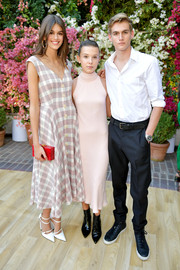 Millie Bobby Brown contrasted her sweet dress with edgy black ankle boots, also by Calvin Klein.