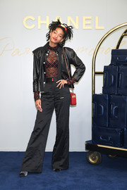 Willow Smith layered a black leather jacket over a sheer top for the Chanel Metiers D'art Collection Paris Cosmopolite show.