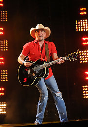 Jason Aldean strummed his guitar in ripped up denim. A cowboy completes the country look.