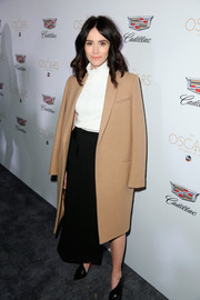 Abigail Spencer arrived for Cadillac's Oscar week celebration wearing a beige wool coat over a white turtleneck and a black skirt.